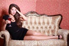 La muchacha sostiene el vidrio con el vino rojo y se sienta en el sofá Imagen de archivo libre de regalías