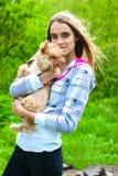 La muchacha sostiene en sus manos un pequeño perro Imagen de archivo