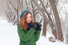 La muchacha sostiene la cámara retra negra en el día de invierno Imagenes de archivo