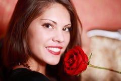 La muchacha sostiene la rosa del rojo cerca de la cara Fotos de archivo libres de regalías