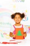 La muchacha sostiene la tarjeta del cartón con el árbol de Navidad y se coloca Fotos de archivo