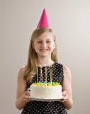 La muchacha sostiene la torta de cumpleaños con las velas encendidas Foto de archivo