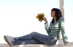 La muchacha sostiene las hojas del otoño Fotos de archivo