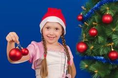 La muchacha sostiene los juguetes del Año Nuevo disponibles y sonríe Imágenes de archivo libres de regalías