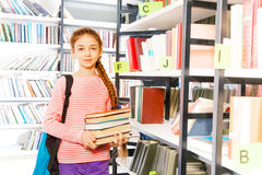 La muchacha sostiene los libros cerca del estante en biblioteca Fotos de archivo