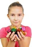 La muchacha sostiene los regalos minúsculos Fotos de archivo