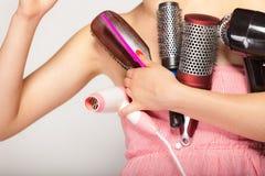 La muchacha sostiene muchos accesorios para diseñar del pelo Imagen de archivo
