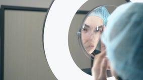 La muchacha sostiene la regla de la frente y mira en espejo el tatuaje fresco almacen de video