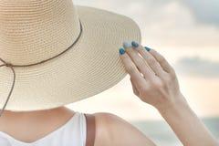 La muchacha sostiene sombrero con su mano Cierre para arriba Visión posterior Fotografía de archivo libre de regalías