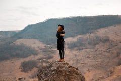 La muchacha sostiene sombrero, dándole vuelta de nuevo al valle con las montañas estancia en roca imagen de archivo libre de regalías