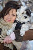 La muchacha sostiene su pequeño perro vestido Foto de archivo
