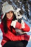 La muchacha sostiene su pequeño perro vestido Imagen de archivo libre de regalías