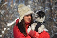 La muchacha sostiene su pequeño perro vestido Fotos de archivo libres de regalías
