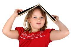La muchacha sostiene un libro en su cabeza aislada en blanco Foto de archivo libre de regalías