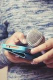 La muchacha sostiene un micrófono en su mano y busca una canción en el teléfono para el funcionamiento del Karaoke imagenes de archivo
