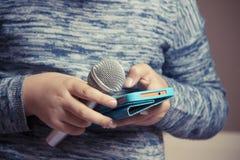 La muchacha sostiene un micrófono en su mano y busca una canción en el teléfono para el funcionamiento del Karaoke fotos de archivo libres de regalías