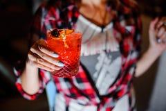 La muchacha sostiene un nergoni alcohólico del cóctel adornado con la naranja y la cereza secadas Imágenes de archivo libres de regalías