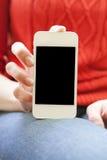 La muchacha sostiene un smartphone en la mano Imagen de archivo