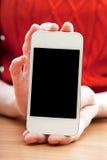 La muchacha sostiene un smartphone en manos Imagen de archivo libre de regalías
