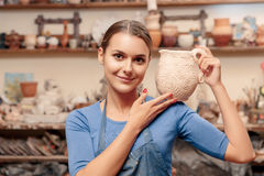 La muchacha sostiene un tarro de la arcilla Imágenes de archivo libres de regalías