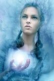 La muchacha sostiene una esfera que brilla intensamente de cristal Foto de archivo libre de regalías