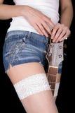 La muchacha sostiene una guitarra entre sus piernas Foto de archivo libre de regalías