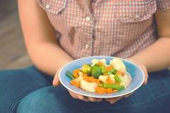 La muchacha sostiene una placa con las verduras Imagen de archivo