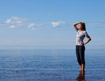 La muchacha staing en el mar con los ojos cerrados Fotografía de archivo libre de regalías
