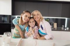 La muchacha, su madre y su abuela están presentando en la cocina para hacer una torta hecha en casa Imagenes de archivo
