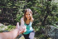 La muchacha sube en la roca, socio saca la mano para la ayuda fotografía de archivo