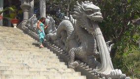 La muchacha sube para arriba las escaleras escalera adornada con las estatuas de dragones metrajes