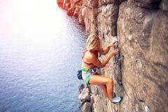 La muchacha sube la roca fotografía de archivo