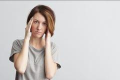 La muchacha sufre de dolores de cabeza terribles y comprime la cabeza con los fingeres fotos de archivo