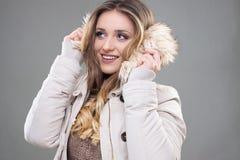La muchacha tímida agradable del inconformista en invierno viste, la chaqueta poner crema con la piel, b Fotos de archivo