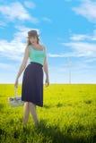 La muchacha tímida lleva una cesta a lo largo de los molinoes de viento imagenes de archivo