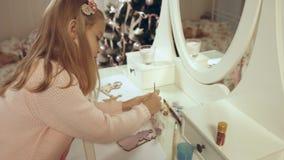 La muchacha talentosa pinta un juguete de madera plano en el árbol de navidad Fotos de archivo libres de regalías