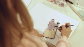 La muchacha talentosa pinta un juguete de madera plano en el árbol de navidad Imagen de archivo
