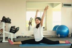 La muchacha tiene clase de la yoga de la lección que estira ejercicio imagen de archivo libre de regalías