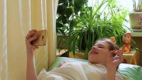 La muchacha tiene llamada del videa Ondas adolescentes que su mano habla y que sonríe mintiendo en cama metrajes