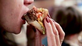 La muchacha tiene un cheeseburger Muerde un primer de la hamburguesa almacen de video