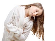 La muchacha tiene un dolor de estómago con la albornoz, en el backgrou blanco Imagenes de archivo