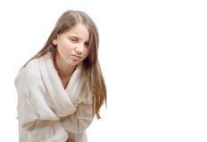 La muchacha tiene un dolor de estómago con la albornoz, en el backgrou blanco Fotografía de archivo libre de regalías