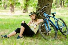La muchacha tiene un resto en el bosque después de que un paseo de la bici Imagenes de archivo