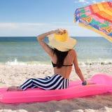 La muchacha tiene un resto en la playa Imagen de archivo