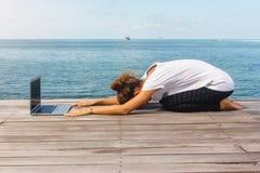 La muchacha tiene una práctica de la yoga en el piso de madera con el ordenador portátil foto de archivo