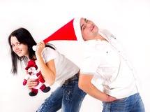 La muchacha tira del casquillo de Santa encima. Días de fiesta Imagenes de archivo