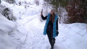 La muchacha tira el vídeo en un bosque nevoso del invierno que ella es feliz Una muchacha está registrando el vídeo en un smartph almacen de metraje de vídeo