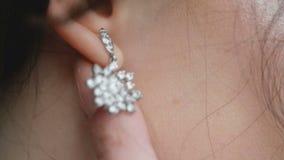 La muchacha tocó el pendiente con el diamante almacen de video