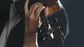 La muchacha toca el violín una composición en un cuarto ahumado oscuro Cierre para arriba metrajes