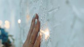 La muchacha toca la pared con una mano, entre las pequeñas lámparas, primer almacen de metraje de vídeo